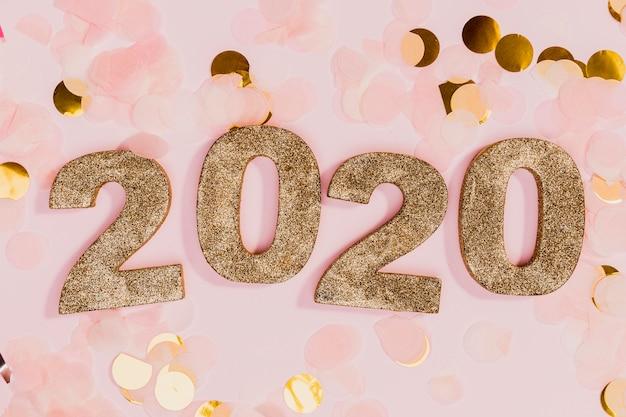Signe du nouvel an avec des confettis or et rose