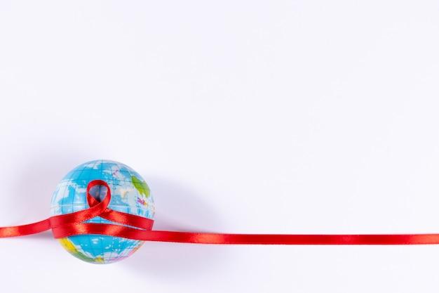 Signe du sida et ruban rouge enroulé autour du globe