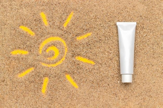 Signe du soleil dessiné sur le sable et blanc tube de crème solaire.