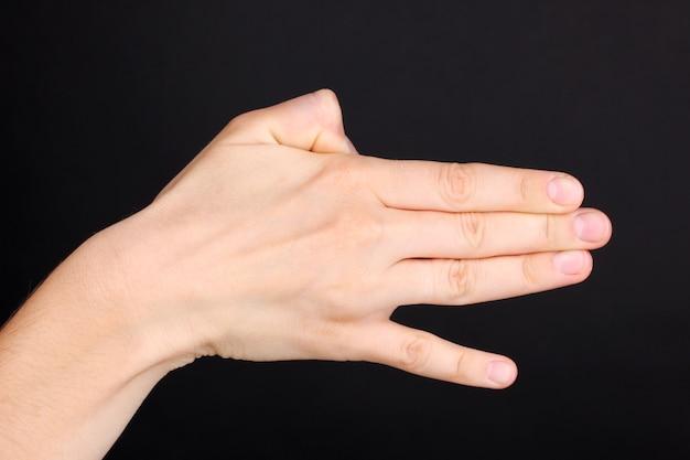 Signe de fabrication de main isolé sur noir