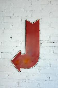 Signe de la flèche gauche sur le mur de briques blanches, fond de bloc avec le signe de la flèche