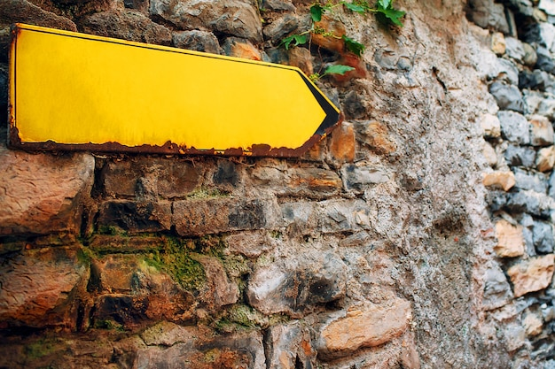 Signe de flèche jaune sur le vieux mur de briques en pierre. pointeur de direction avec espace de copie vide.