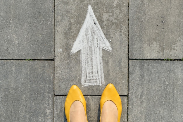 Signe de flèche peinte sur un trottoir gris avec des jambes de femmes