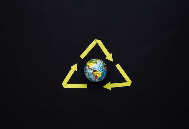 Signe de flèches recyclées et globe sur fond noir. sauvez la planète. vue de dessus