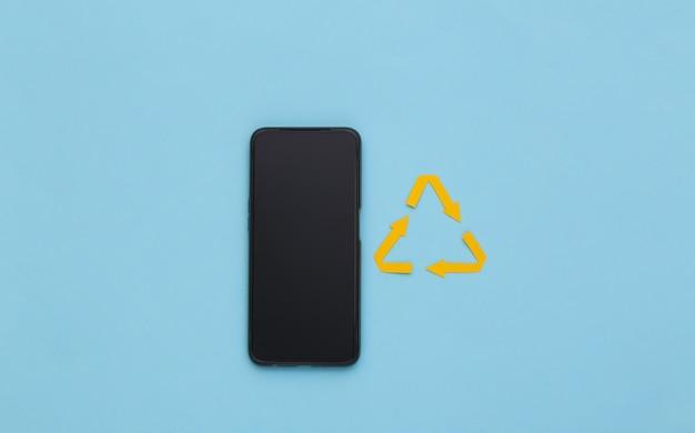 Signe de flèches recyclées et smartphone sur fond bleu. vue de dessus