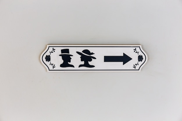 Signe d'icône de toilettes en bois avec flèche de direction et symbole masculin et féminin