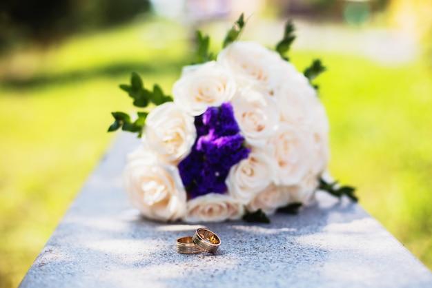 Signe de l'infini des anneaux, anneaux de mariage sur un blanc, alliances, anneaux de mariage se trouvent près de bouquet de roses blanches et roses, pêche, un bouquet de roses, fleurs de mariage