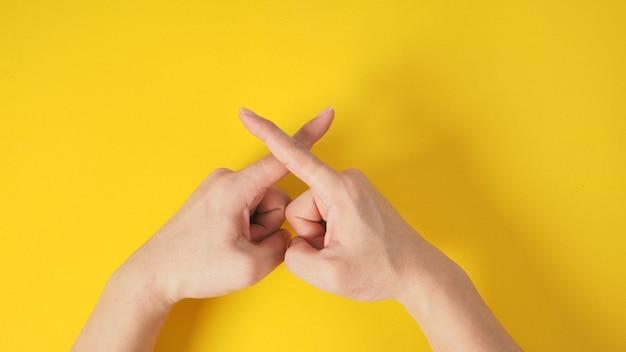 Signe de main interdit ou de rejet sur fond jaune.