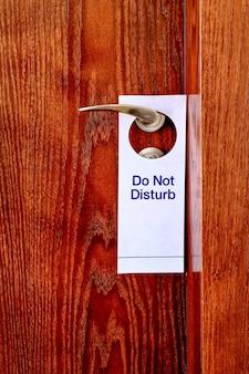 Le signe ne pas déranger est accroché à la poignée de porte. ne pas déranger signe à la porte de la chambre d'hôtel. fermer