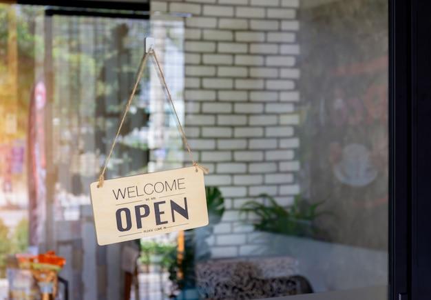 Signe ouvert en bois large à travers le verre de la fenêtre au café