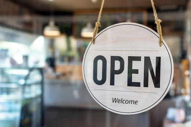 Signe ouvert de café sur le panneau d'affichage vintage accroché à la porte en verre