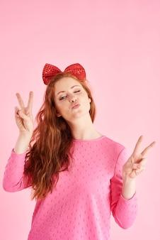Signe de paix fait par la jeune femme au projectile de studio