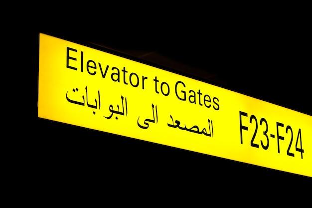 Signe de porte dans un aéroport international au moyen-orient avec des informations en arabe