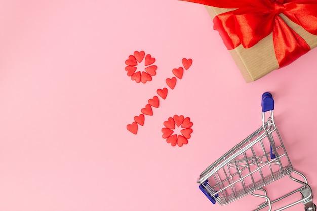 Signe de pourcentage bordé de petits coeurs rouges avec cadeau emballé dans du papier kraft et ruban rouge et panier sur fond rose. mise à plat. copiez l'espace.