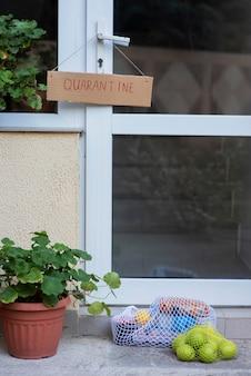 Signe de quarantaine sur la porte d'entrée avec des produits d'épicerie