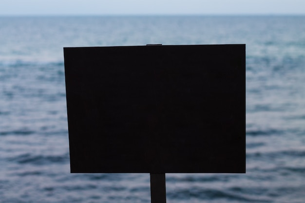 Signe rectangulaire noir vide avec la mer sur le fond
