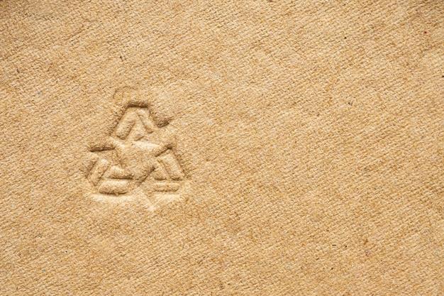 Signe de recyclage sur fond de texture de papier carton brun