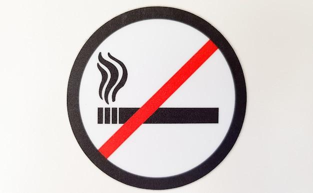 Signe rond rouge et noir d'interdiction de fumer, autocollant dans un lieu public sur fond blanc.