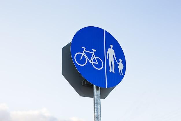 Signe rond de voie cyclable contre un ciel bleu