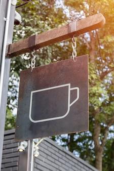 Signe de tasse de café accroché sur la barre de bois