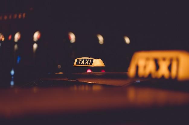 Signe de taxi sur fond de nuit de ville floue