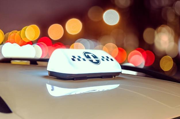 Signe de taxi sur le toit de la voiture qui brille dans les lumières colorées floues floues du trafic dans la ville, la ville de nuit avec boken