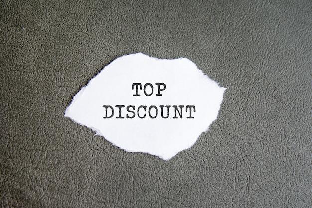 Signe top discount sur le papier déchiré sur fond gris.
