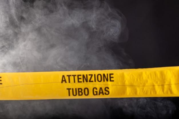 Signe d'urgence jaune d'attention tuyau de gaz sur fond rempli de fumée. sur le ruban jaune la mention écrite