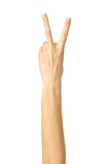 Signe de la victoire. main de femme avec manucure française gesticulant isolé sur fond blanc. fait partie de la série