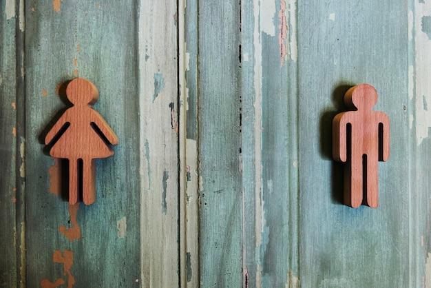 Signes de genre de toilette sur le mur en bois