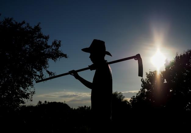 Silhouette d'un agriculteur avec coucher de soleil dans le paysage de la nature