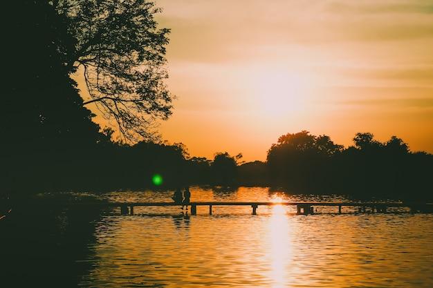 Silhouette arrière d'un couple sur le pont magnifique lac de la forêt au fond du coucher de soleil