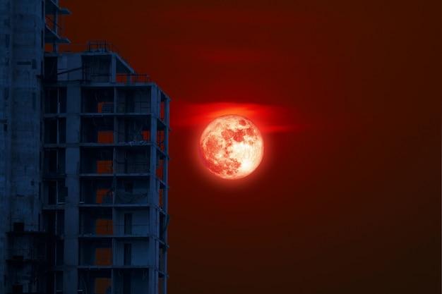 La silhouette arrière de la lune de sang à grain complet abandonne la construction sur le ciel nocturne, éléments de cette image fournis par la nasa