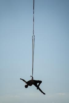 Silhouette d'artiste de cirque sur les sangles aériennes sur fond de ciel bleu