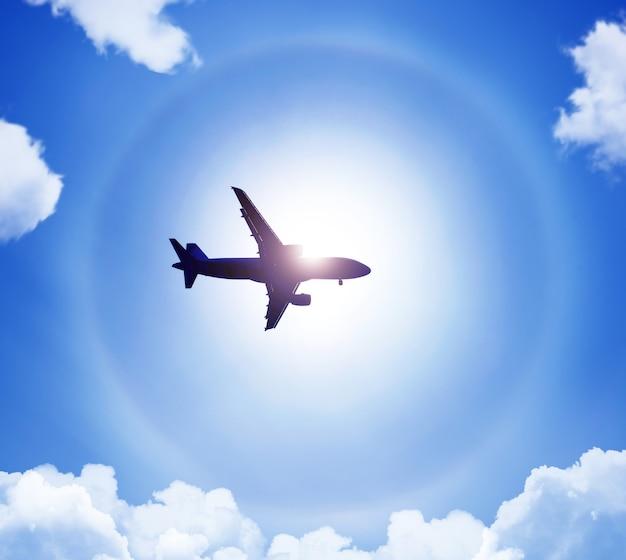 Silhouette d'un avion dans le ciel soleil et halo dans les nuages.