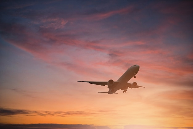 Silhouette d'avion voler sur le ciel pendant le coucher du soleil.