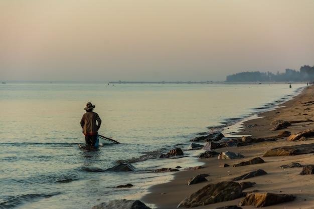 Silhouette de bateau de pêche et de pêcheur au lever du soleil en thaïlande