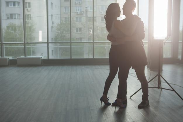 Silhouette de beau couple dansant et appréciant la musique. instant passionné. danseurs habiles.