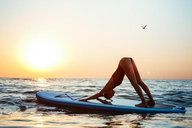 Silhouette de belle femme pratiquant le yoga sur planche de surf au lever du soleil.