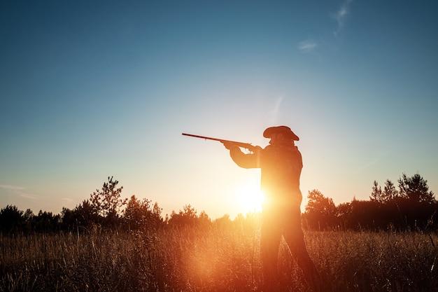 Silhouette de chasseur dans un chapeau de cowboy avec une arme à feu dans ses mains sur un beau coucher de soleil