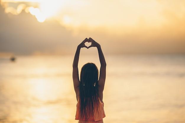 Silhouette de coeur faite par la main d'enfants au coucher du soleil