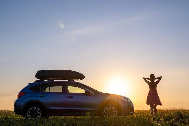 Silhouette d'une conductrice debout près de sa voiture sur un terrain herbeux, profitant d'une vue sur le coucher de soleil lumineux. jeune femme se détendre pendant un voyage sur la route à côté d'un véhicule suv.