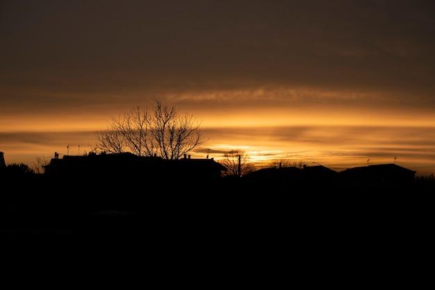 Silhouette d'un coucher de soleil rouge dans un village pendant la période hivernale