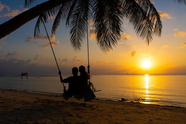 Silhouette de couple amoureux se promène sur la plage pendant le coucher du soleil. monter sur une balançoire attachée à un palmier et regarder le soleil se coucher dans l'océan
