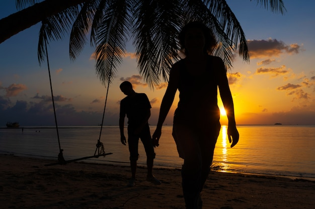 Silhouette de couple amoureux se promène sur la plage pendant le coucher du soleil.