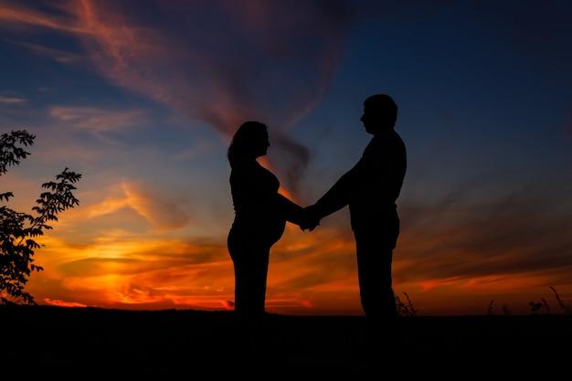 Silhouette d'un couple en attente de bébé sur ciel coucher de soleil