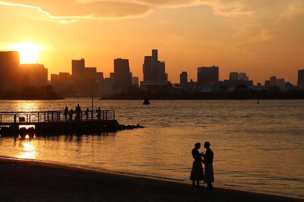 Silhouette couple et bâtiments en bord de mer, structure multiple sur ciel coucher de soleil