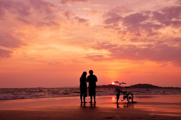 Silhouette, couple, debout, plage, dramatique, coucher soleil, ciel