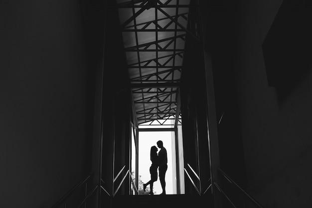 Silhouette d'un couple sur lumineux au bout d'un tunnel piétonnier souterrain
