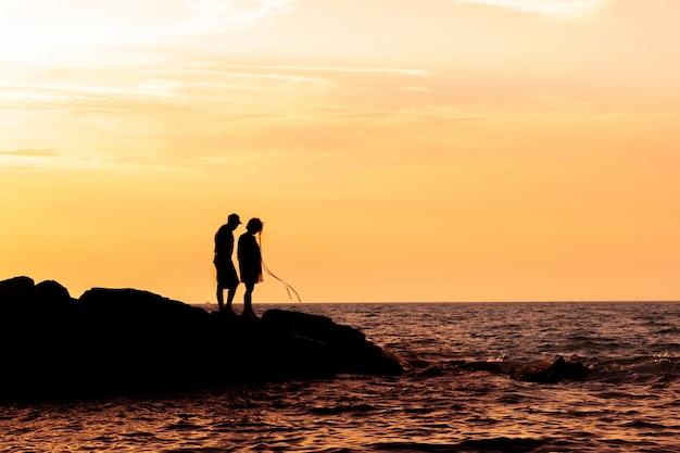Silhouette de couple sur la plage avec un beau coucher de soleil